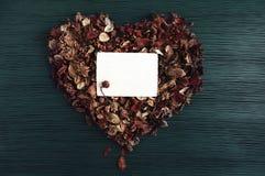 与心脏的背景从干燥芬芳花和一张空的照片 免版税库存图片
