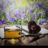 与心脏礼物、笔记本和笔的茶时间在木桌上 免版税库存照片