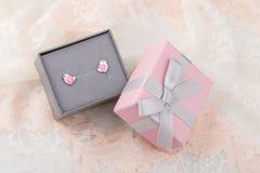 与心脏耳环螺柱的鸟形状在鞋带ba的桃红色礼物盒 库存图片