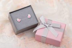 与心脏耳环螺柱的鸟形状在鞋带ba的桃红色礼物盒 免版税库存图片