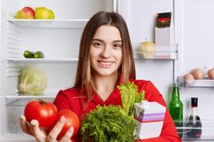 与快乐的表示的宜人的看起来的女性模型拿着她在菜市场` s商店买的新鲜蔬菜,站立近的opene 免版税库存图片