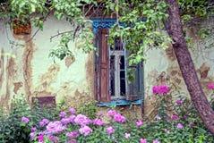 与快门的一个老窗口在一个农村房子的墙壁上在庭院和花里 免版税库存图片