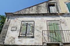 与快门的老遗弃大厦在窗口, Assos, kefalonia,希腊 库存图片