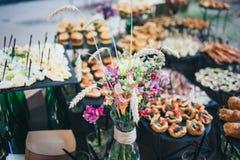 与快餐的美丽的在桌上的宴会桌和花束 图库摄影