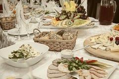 与快餐,果子,沙拉的装饰的桌 免版税库存照片