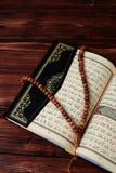 与念珠小珠的伊斯兰教的圣经古兰经在木桌背景 Kuran圣经os穆斯林 E 库存图片