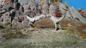 与恐龙石雕塑的秋天风景  免版税库存图片