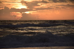 与恼怒的海浪的日出 免版税库存照片
