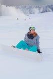 与您的雪板的女孩过大的开会在雪 库存图片