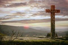 与惊人的天空的石十字架在日落 免版税库存图片