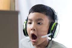 与惊奇的面孔的亚洲孩子戏剧计算机游戏 库存照片