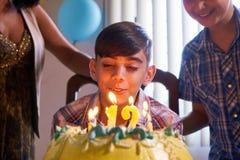 与愉快的拉丁美州的男孩吹的蜡烛的生日聚会在蛋糕 免版税库存照片