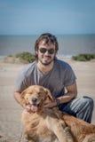 与愉快的狗金毛猎犬品种的年轻男性在海滩 图库摄影
