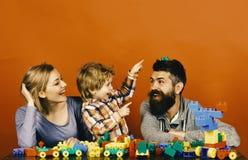 与愉快的面孔修造玩具汽车的家庭在色的建筑块外面 父母身分和比赛概念 刮胡须人 免版税库存照片