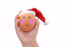 与愉快的面孔的圣诞节鸡蛋在手中的儿童白色背景 免版税图库摄影
