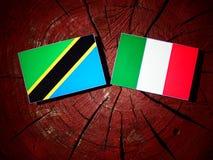 与意大利旗子的坦桑尼亚的旗子在被隔绝的树桩 库存例证