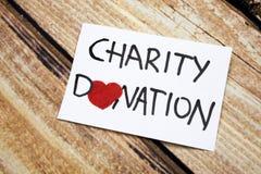 与慈善捐赠手写的消息的概念性图象在白皮书有木背景 健康和神将概念 库存图片