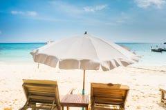与懒人和伞的完善的海滩场面 免版税库存图片