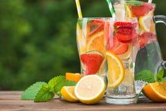 与成份、柠檬、草莓和桔子的柠檬水鸡尾酒 库存照片