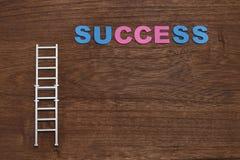 与成功词的事业梯子在木头 库存照片