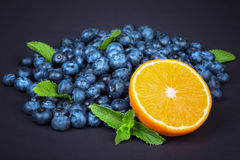 与成熟一半的甜蓝莓橙色和绿色薄菏 与一半的整个蓝莓桔子和薄菏在黑暗的背景 免版税库存照片