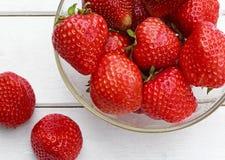 与成熟水多的草莓位置的静物画在盘和关闭 库存图片