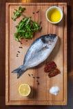 与成份的新鲜的未煮过的dorado鱼在木板 免版税库存图片