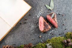 与成份的鹿或鹿肉牛排喜欢海盐、草本和胡椒和厨师书、食物背景餐馆的或狩猎lo 库存图片
