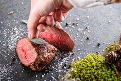 与成份的鹿或鹿肉牛排喜欢海盐、草本和胡椒和手厨师、食物背景餐馆的或狩猎lo 免版税库存图片