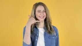 与我们联系,告诉我由年轻俏丽的女孩,黄色背景打手势 股票视频