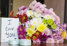 与我爱你卡片和圆环的美丽的菊花花束 免版税库存照片