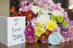 与我爱你卡片和圆环的美丽的菊花花束 免版税图库摄影