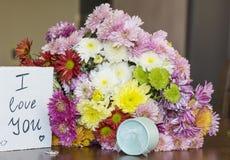 与我爱你卡片和圆环的美丽的菊花花束 库存图片