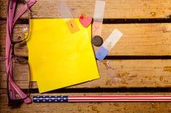 与我爱你字母表的黄色白纸与桃红色玻璃和铅笔在木pettern 免版税库存图片