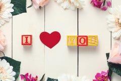 与我爱你立方体的红色心脏在木桌上 免版税库存图片