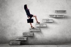 与战略文本的女实业家上升的梯子 免版税库存图片