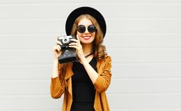 与戴一个典雅的帽子,棕色夹克的减速火箭的影片照相机的愉快的凉快的少妇模型 免版税库存照片