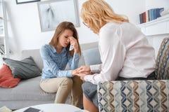 与户内坐女孩哭泣的抹的客户的女性psychologyst疗期撕毁  免版税库存照片