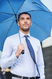 与户外伞的年轻严肃的商人 免版税图库摄影