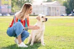 与户外所有者的逗人喜爱的拉布拉多猎犬 免版税库存图片