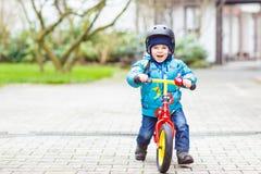 与户外他的第一辆自行车的小男孩骑马 免版税库存照片