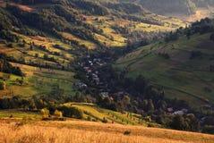 与房子、晴朗的小山和许多小干草堆的一个美好的夏天农村风景 在日落的喀尔巴阡山脉的辗压风景 库存照片