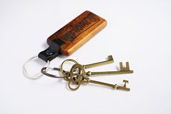 与房子木钥匙圈的古色古香的钥匙有白色背景 免版税图库摄影