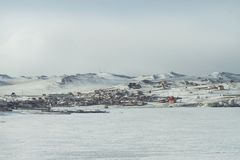 与房子的一个农村风景在贝加尔湖岸和船的冬天在多雪的多山背景的冰 免版税图库摄影