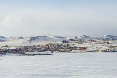 与房子的村庄风景在贝加尔湖岸和船的冬天在多雪的多山背景的冰 免版税图库摄影