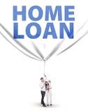 与房屋贷款横幅的年轻家庭 库存照片