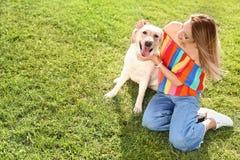 与所有者的逗人喜爱的黄色拉布拉多猎犬 库存照片