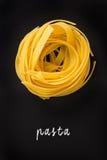 与手书面的字法文本的未加工的黄色tagliatelle面团  免版税库存图片