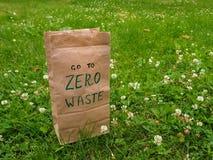与手写的词的一个纸袋'去调零废物'对此在三叶草和绿草中与拷贝空间 库存图片