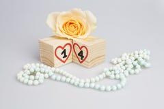 与手写第14的木立方体,心脏,玫瑰色和小珠 免版税库存照片